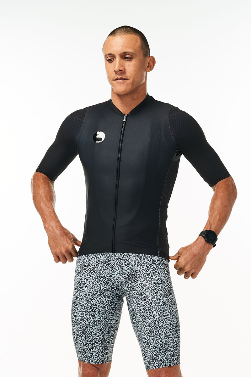 Model wearing men's onyx Hex Racer Jersey with WYN republic Snow Leopard Bib Shorts. Bold cycling kit.