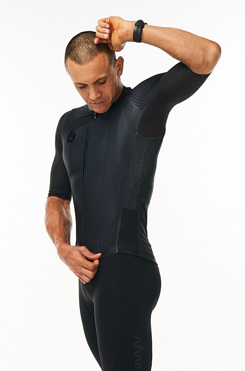 Model lifting left arm of men's Hex Racer Jersey. Flexible black cycling jersey with mesh panels.