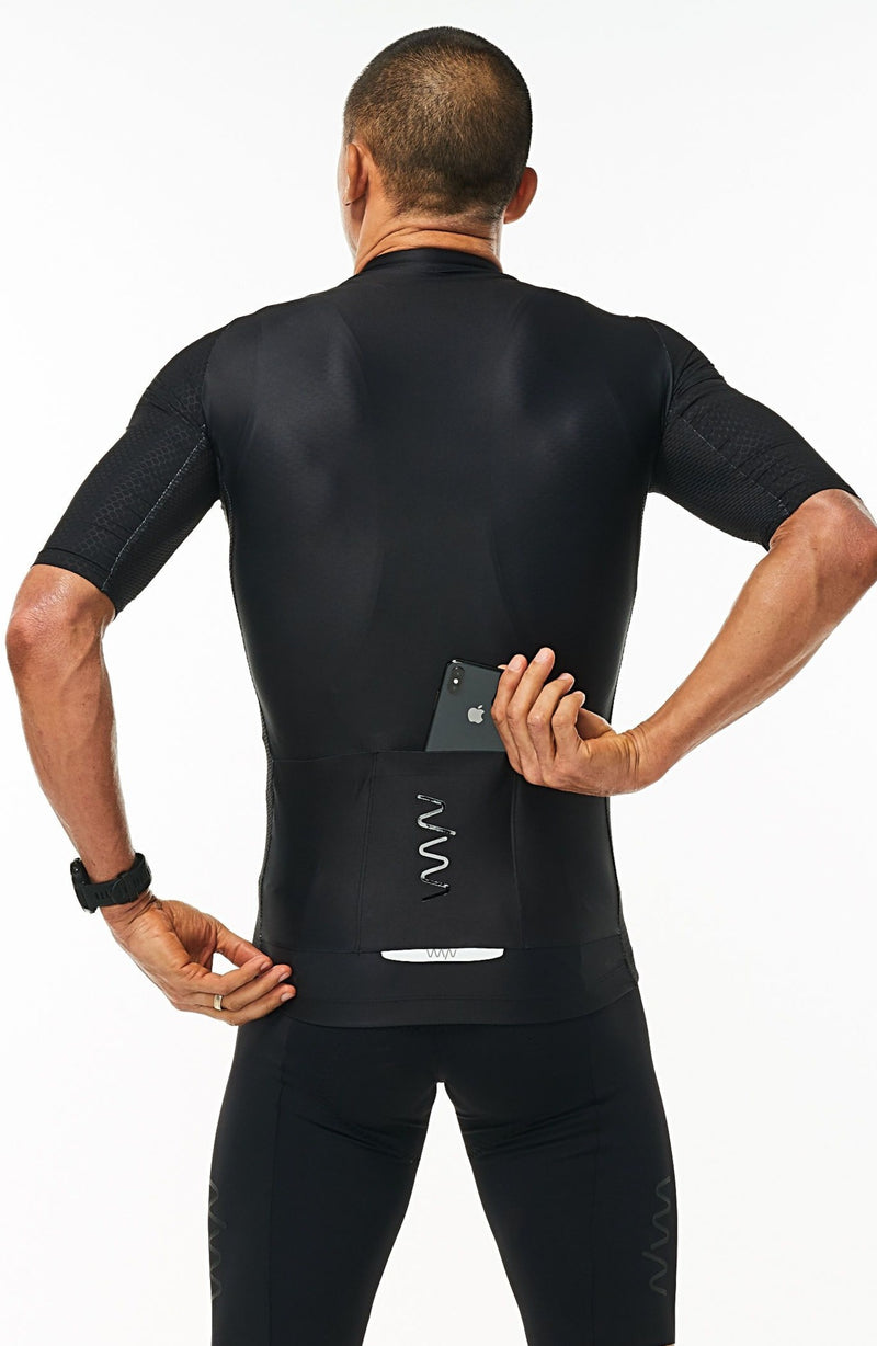 Model placing a phone in the back pockets of men's Onyx Hex Racer Jersey. Black cycling jersey with reflective pockets.