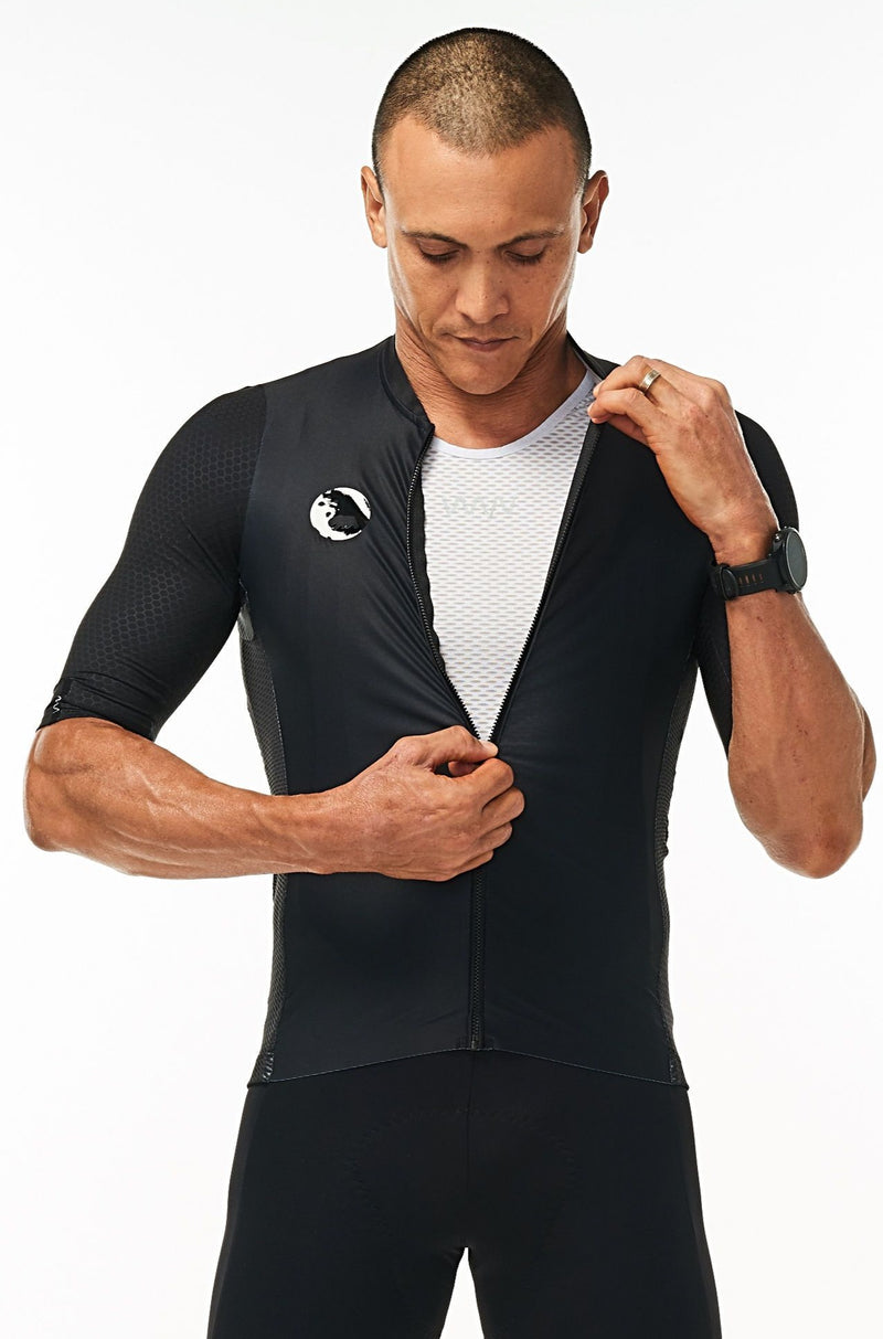Model zipping men's Onyx Hex Racer Jersey. Black cycling jersey with flip-lock zipper.