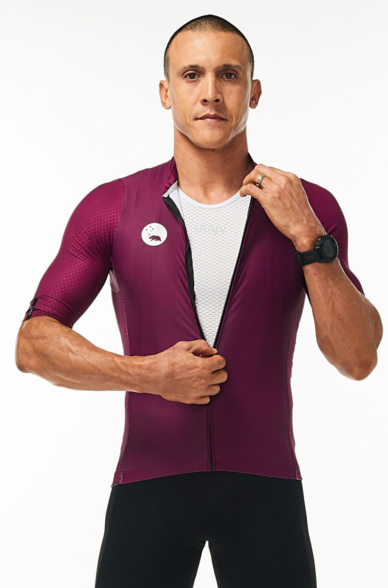 Model zipping men's Tyrian Hex Racer Jersey. Purple cycling jersey with flip-lock zipper.