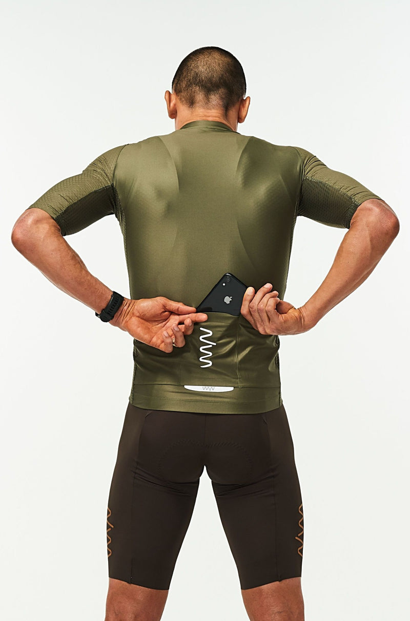 Model placing a phone in the back pockets of men's Olive Hex Racer Jersey. Green cycling jersey with reflective pockets.
