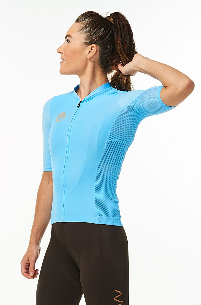 Model lifting left arm of women's Hex Racer Jersey. Flexible blue cycling jersey with mesh panels.