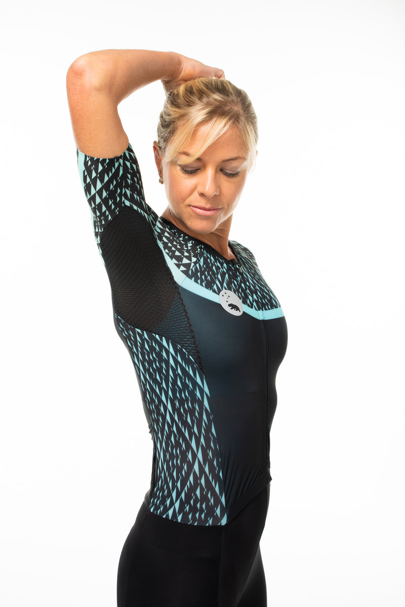 Model lifting right arm of Transcend tri suit. One-piece triathlon suit with ventilated side panels.