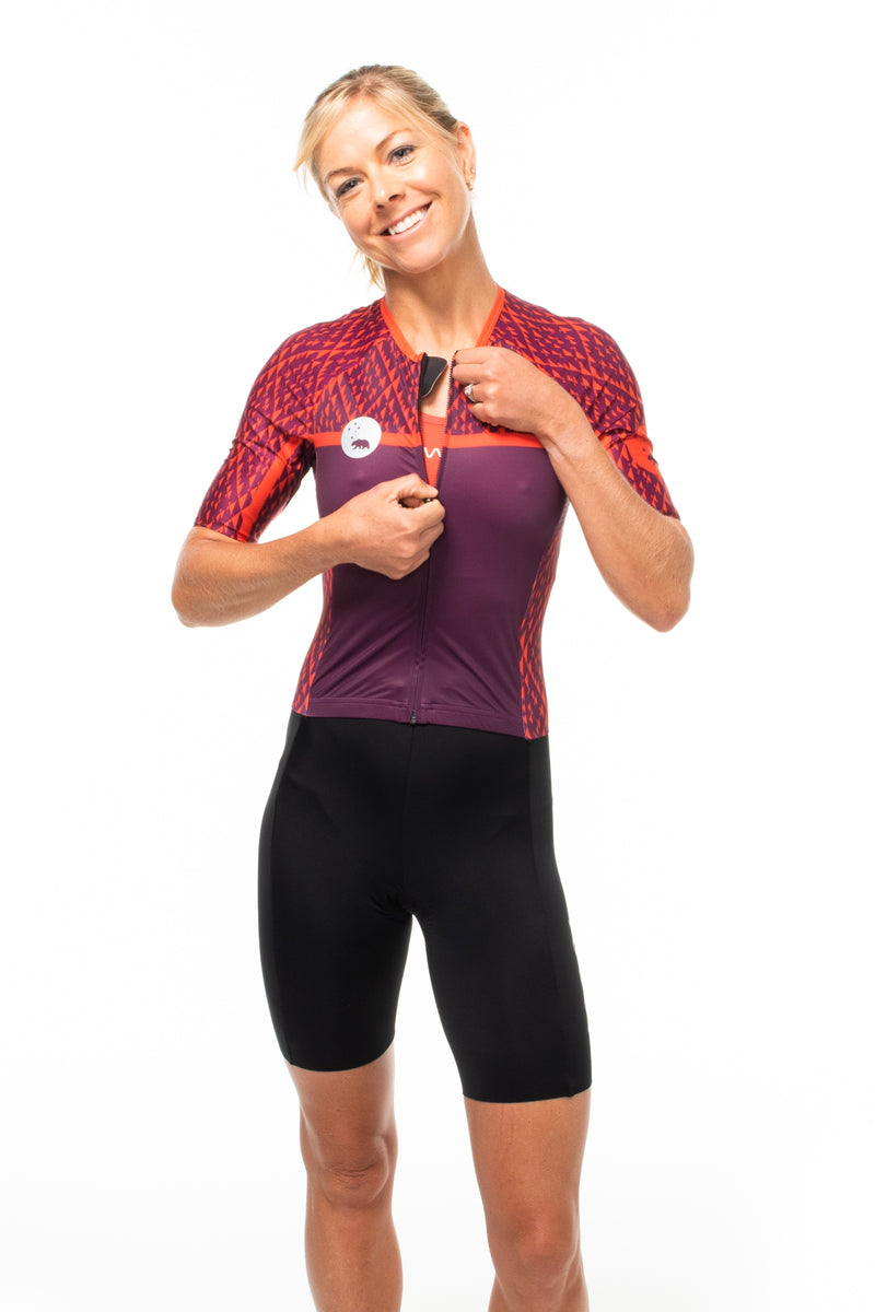 Model zipping women's Rise tri suit. One-piece triathlon suit with full front zipper.