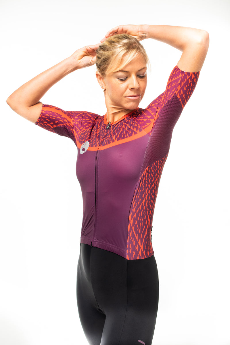 Model lifting left arm in Rise tri suit. Purple and red triathlon suit with mesh ventilation.