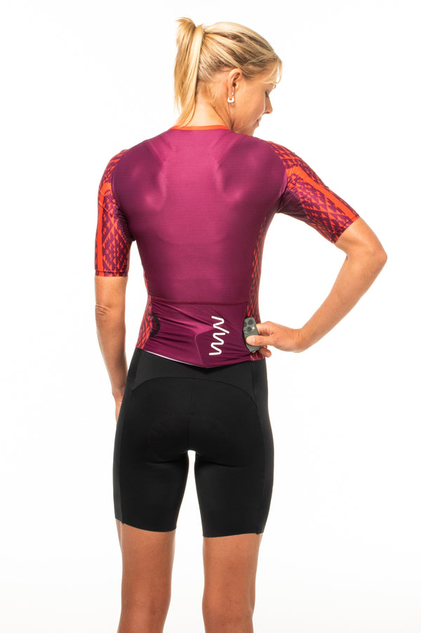 Model placing a phone in side-entry back pocket of women's tri suit. Red triathlon suit with storage.