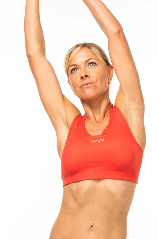 Model lifting arms of hot orange sports bra. Showing flexibility of four-way stretch fabric.