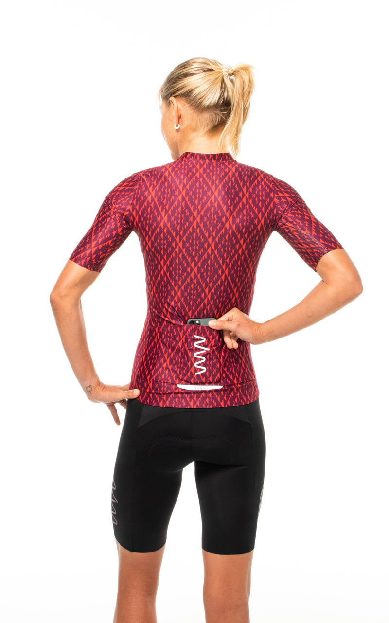 Model placing a phone in back pocket of Rise cycling jersey. Fast red cycling jersey with storage.