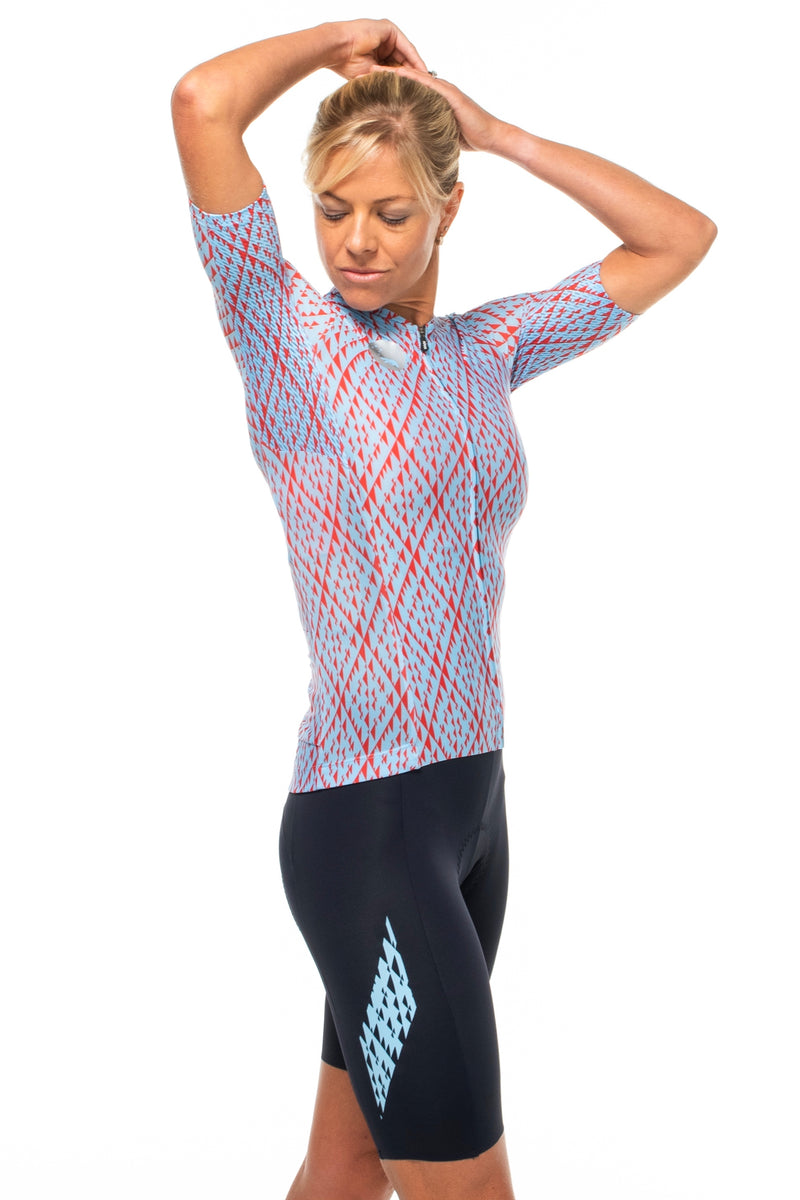 Model lifting right arm of Elevate cycling top. Cycling jersey with ventilated sides.