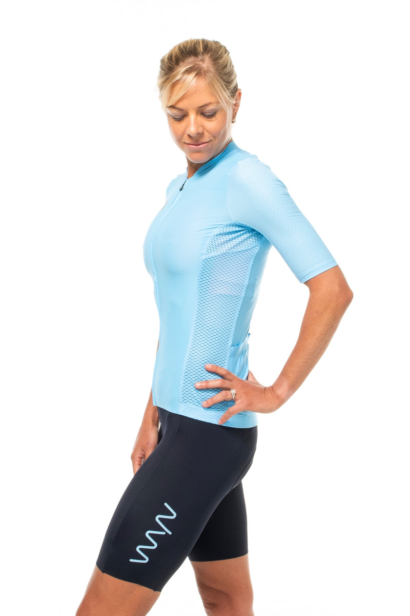 Model wearing Elevate bib shorts with matching blue cycling jersey.