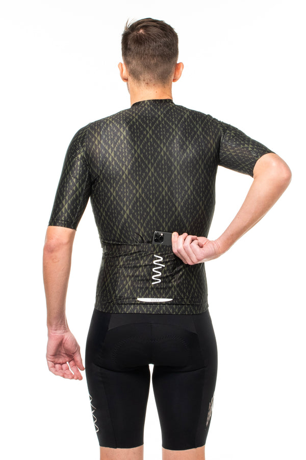 Model placing a phone in back pocket of Surge cycling jersey. Fast green cycling jersey with storage.