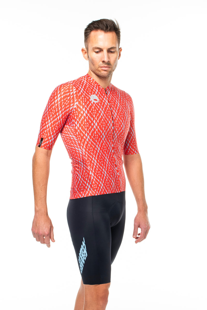 Model wearing Shift bib shorts with red jersey. Matching cycling kit.