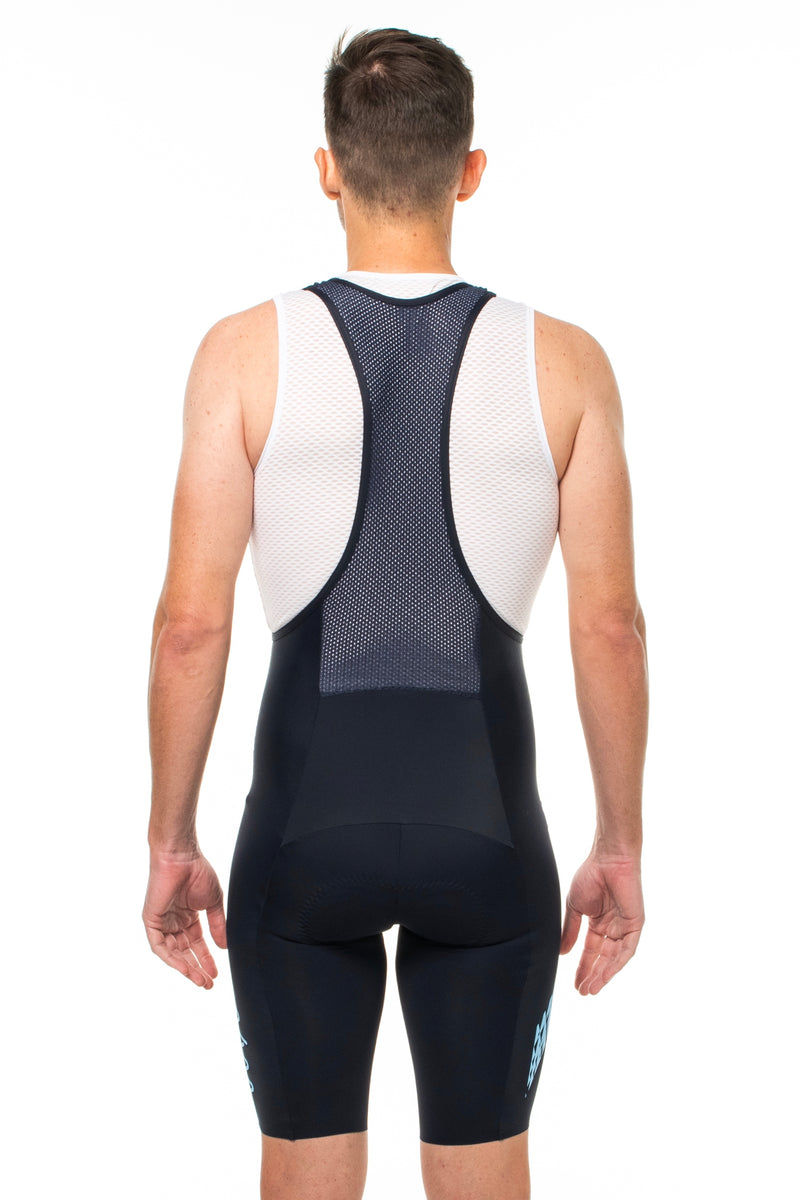 Back view men's Shift bib shorts. Mesh paneling and straps.