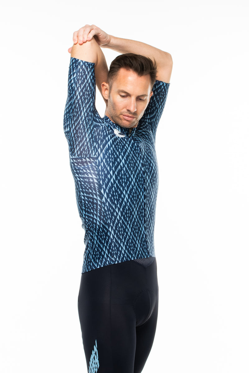 Model lifting right arm of Shift cycling top. Cycling jersey with ventilated sides.