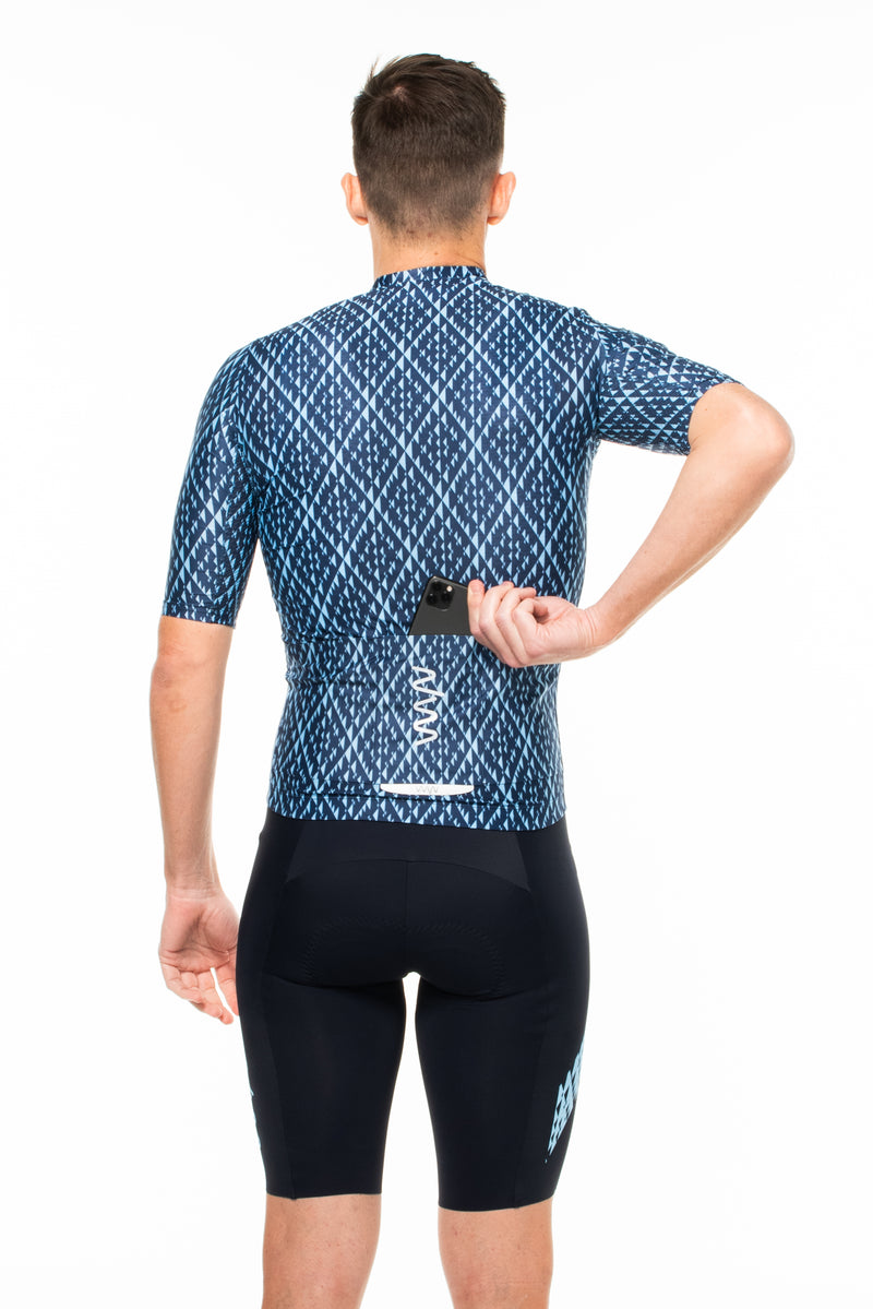 Model placing a phone in back pocket of Shift cycling jersey. Fast cycling jersey with storage.
