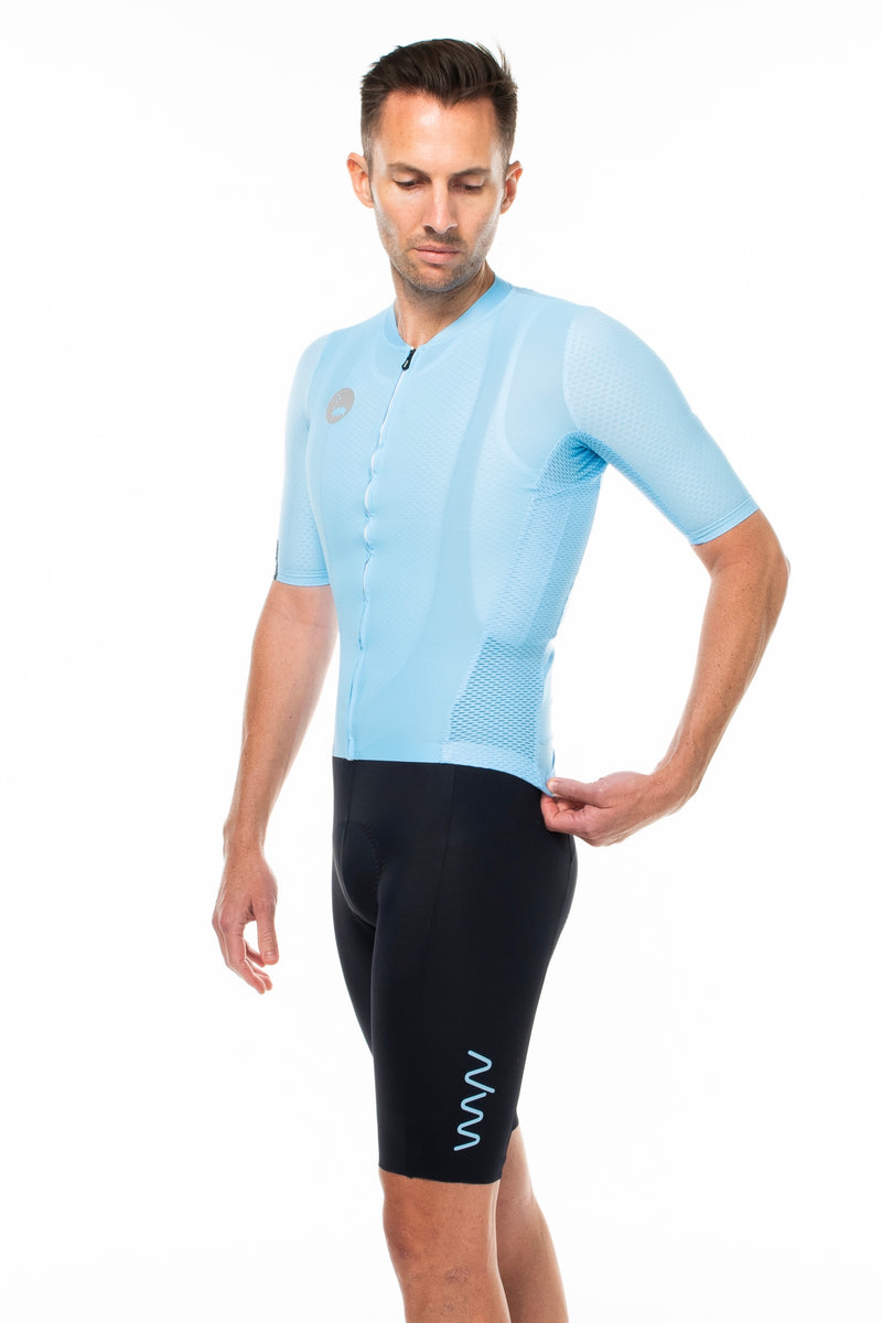 Model wearing Shift bib shorts with blue hex jersey. Matching cycling kit.
