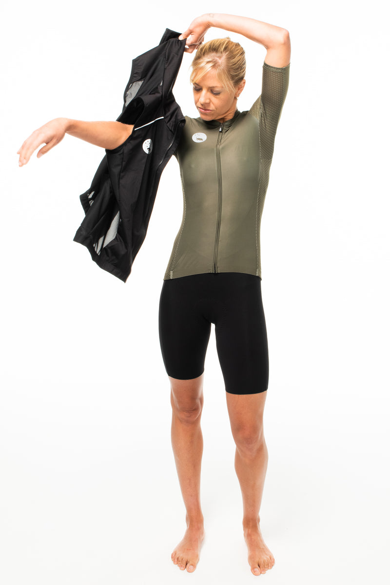 Model putting black wind vest on over olive cycling jersey. Sleeveless top to protect cyclists from wind.