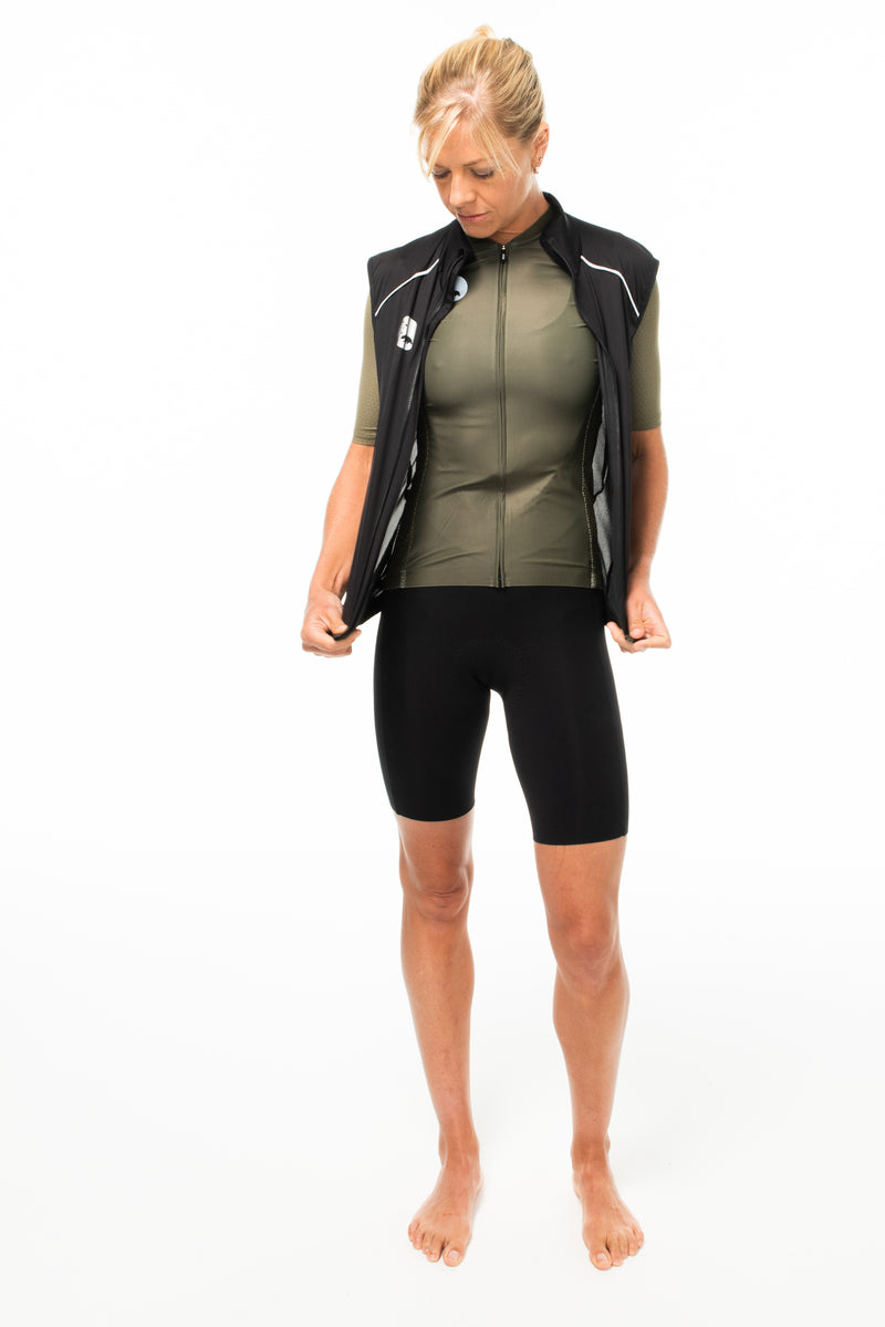 Model wearing unzipped black gilet. Cycling wind vest that fits over cycling jerseys.
