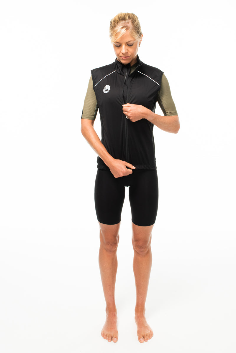 Model zipping WYN republic women's Black Wind Vest. Black cycling gilet with YKK zipper pull.