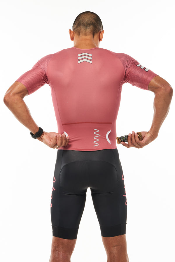Model placing a nutrition gel in side entry back pocket of Code Red men's sleeved tri suit.