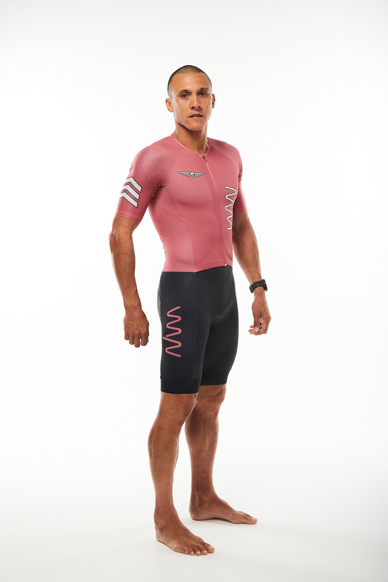Modeling right side men's red tri suit. Three white arrows on sleeve and red WYN logo on thigh.