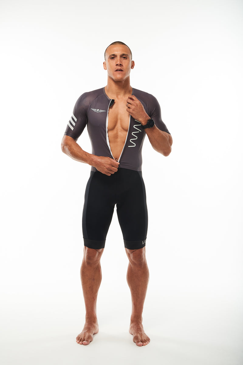 Model unzipping WYN republic men's Zeppelin sleeved tri suit. Aero triathlon suit with fron zipper.