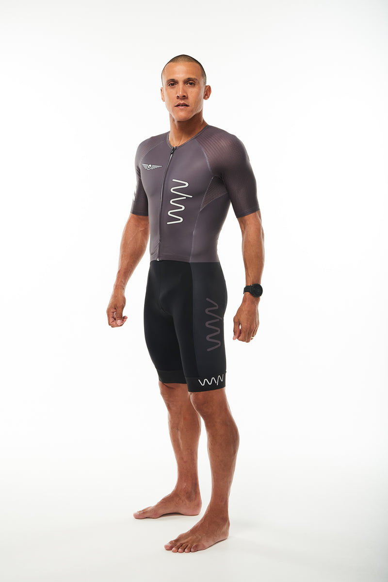 Modeling left side black men's tri suit. White chest logo, grey thigh logo and reflective cuff logo.