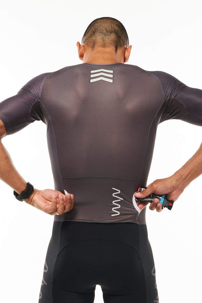 Model placing nutrition gel in side entry back pocket of Zeppelin men's sleeved tri suit.