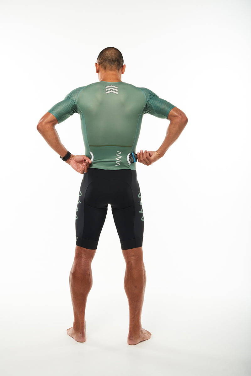 Model placing a nutrition gel in back pocket of men's sleeved tri suit. One-piece tri suit with storage.