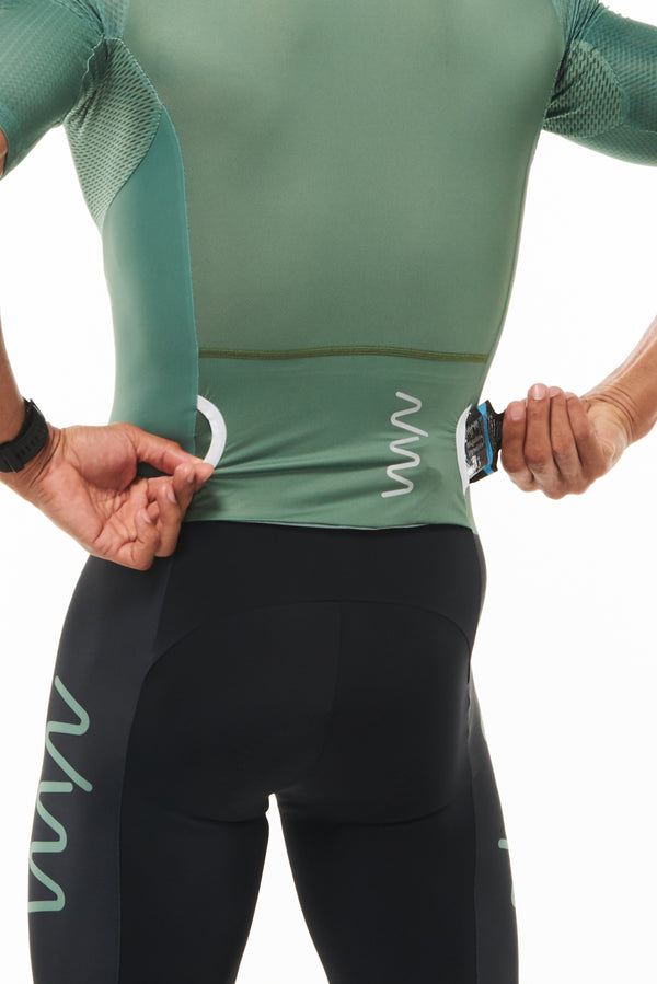 Model placing a phone in side entry back pocket of men's green sleeved tri suit.