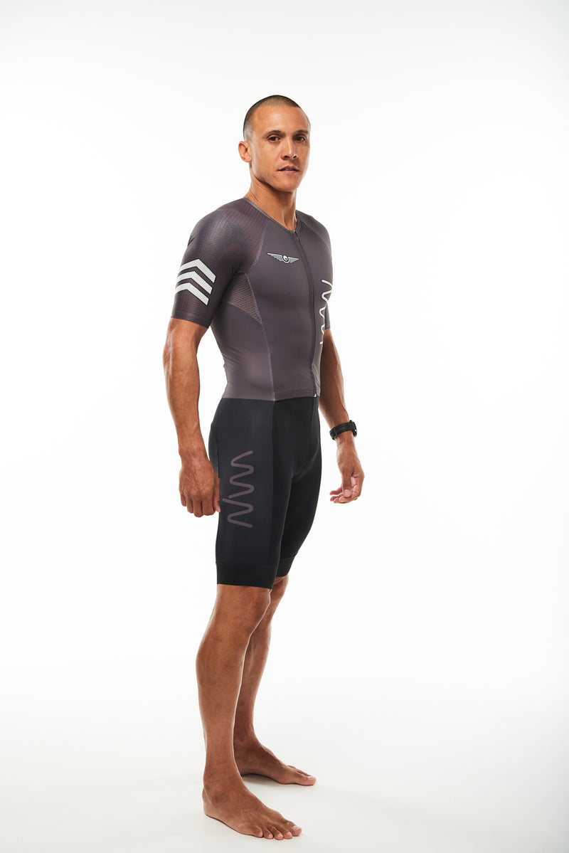 Modeling right side black men's tri suit. Three white arrows on sleeve and grey logo on thigh.