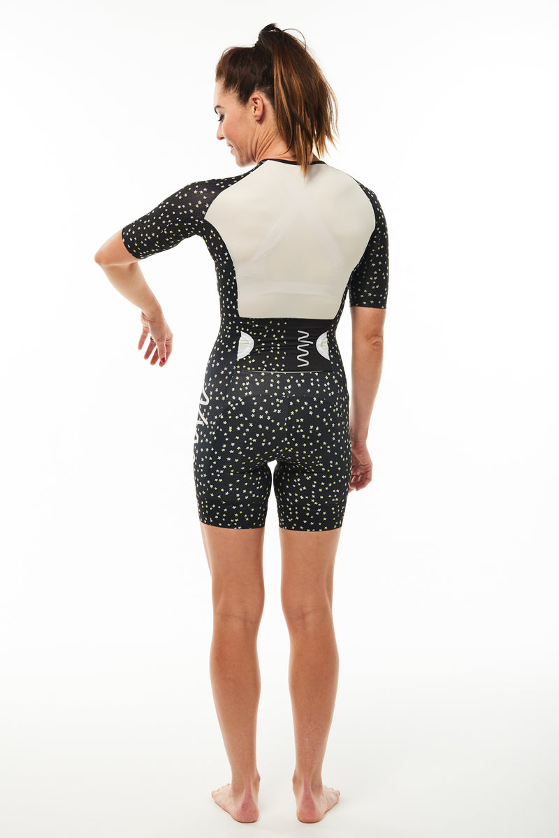 Back view women's Stevie sleeved tri suit. Model lifting arm to show sleeve and back ventilation.