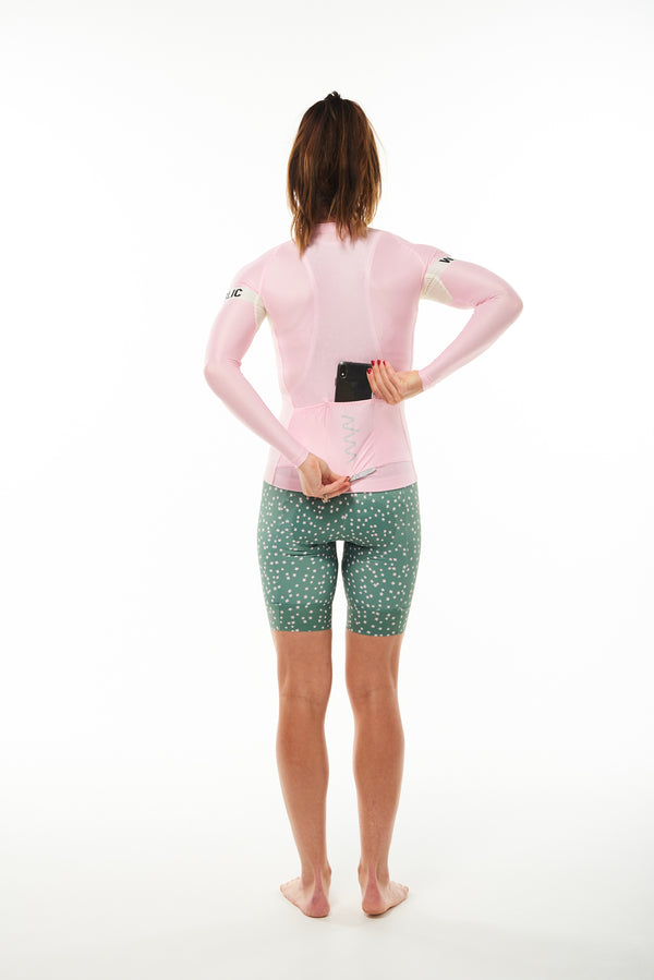 Model placing phone in back pocket of Carly Summer Long Sleeve Jersey. Cycling jersey with storage.