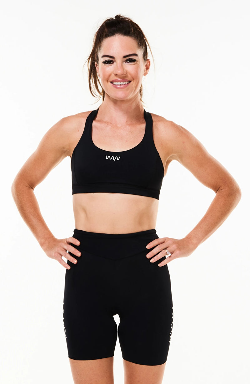 "Model wearing women's Velocity Tri Shorts 5.5"". Black mid-length triathlon shorts."