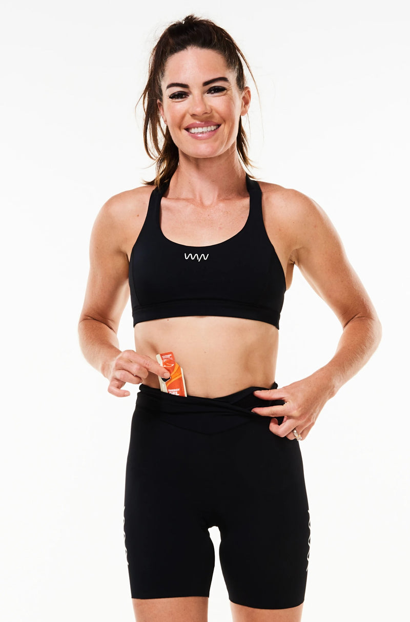 Model placing a nutrition gel in front pocket of women's black tri shorts. Race shorts with storage.