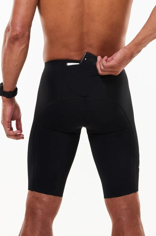 Model placing a phone in large back pocket of men's triathlon shorts. Black aerodynamic tri shorts.