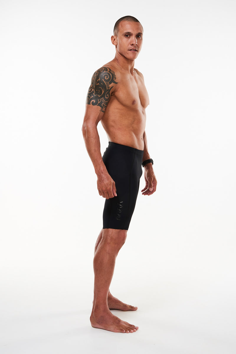 Modeling right side men's Velocity Tri Shorts. Aero shorts with vertical black WYN republic logo.