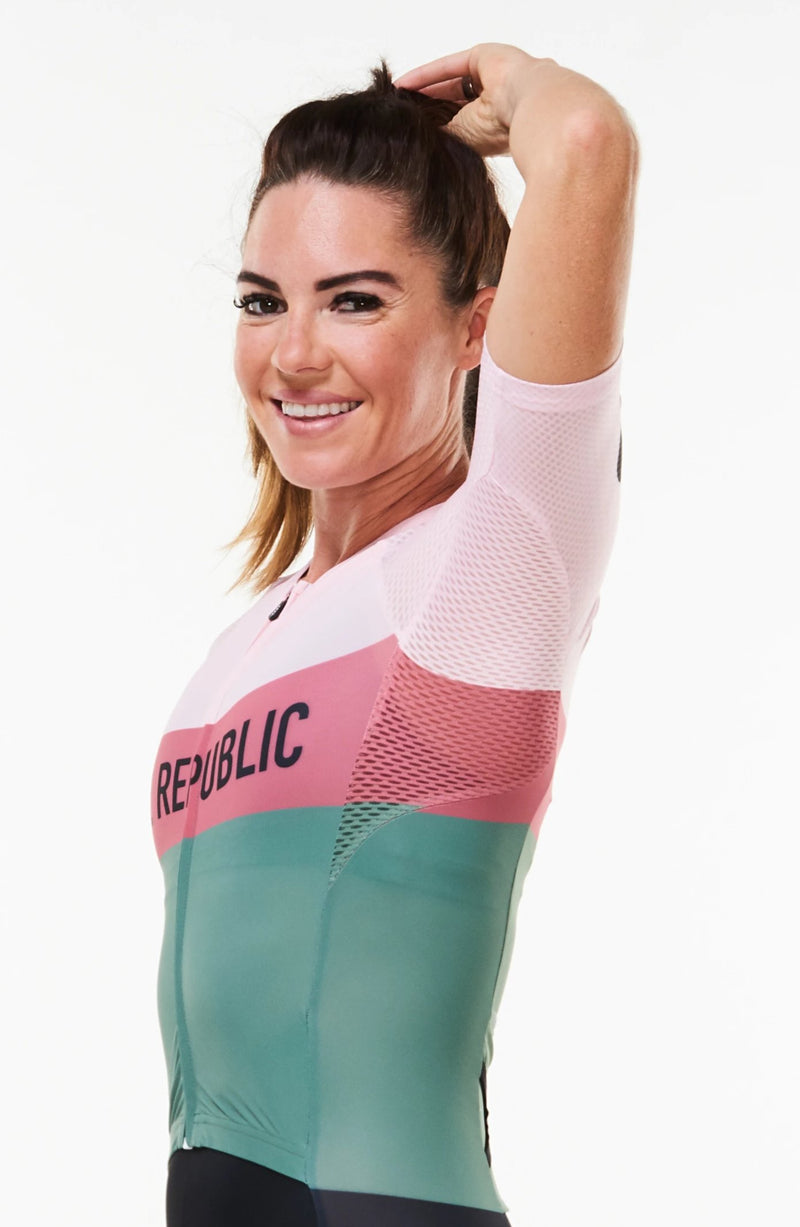 Model raising left arm to show ventilated fabric on sleeves of women's Rebel tri suit.