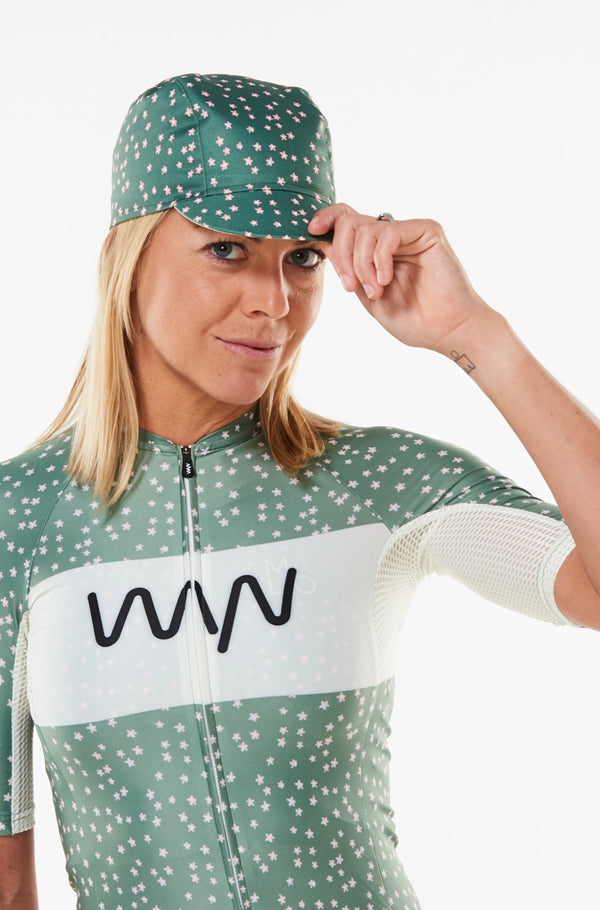 Model wearing WYN republic Janis cycling cap. Green cycling cap with pink daisy print.