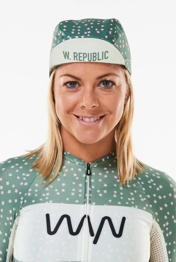 Model wearing WYN republic Janis cycling cap. Brim flipped up showing 'W. REPUBLIC' in green.
