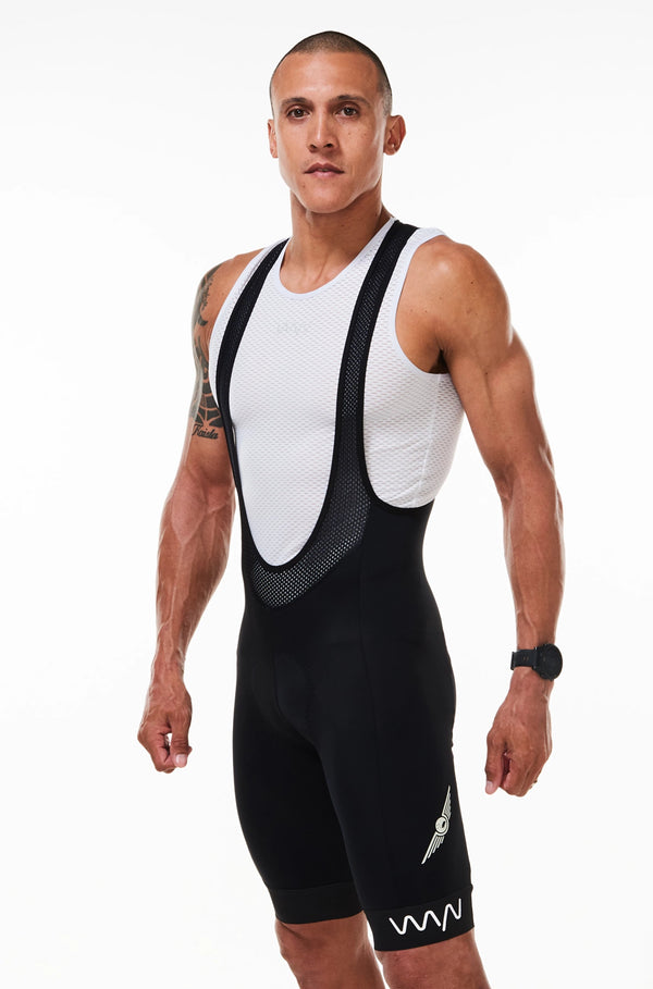 Left angle of model wearing Men's High Flyer Pro Cycling Bib Shorts. Black aerodynamic bib shorts.