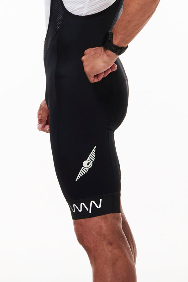 Left side WYN republic men's High Flyer bib shorts. Pilot wings mid-thigh, reflective logo on cuff.