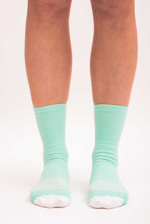 Front view women's Mint/Navy Socks. Green mid-calf running and cycling socks with white toe box.