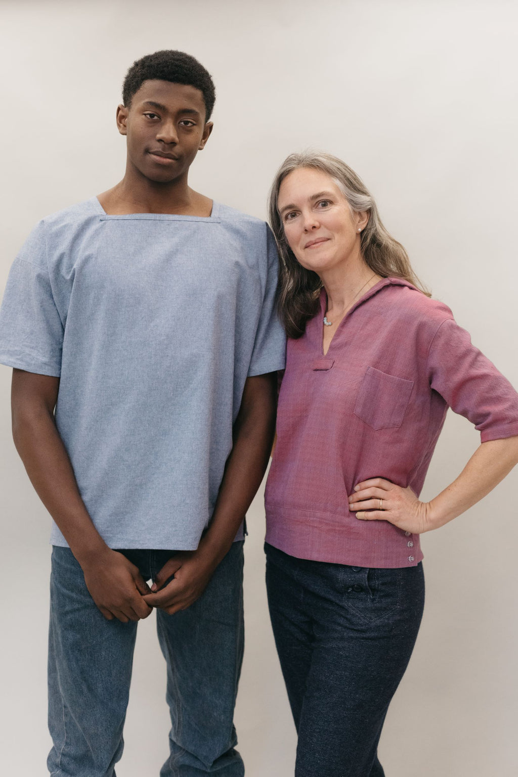 Man and woman wearing middy shirts (one blue and one pink) standing in front of a white background