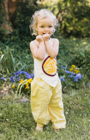 Toddler wearing a kintaro and yellow pants outside.
