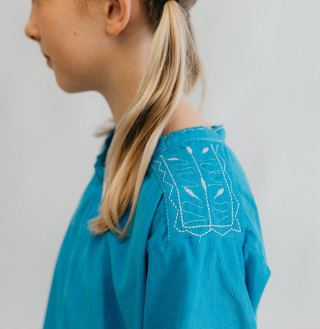 Close up of embroidery on shoulder of blue dress worn by a blond girl