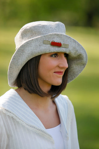 Woman wearing a cream colored hat outside.