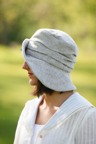 Woman wearing a grey hat facing away from camera.