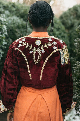 Back of a traditional maroon velvet Bolivian jacket with embroidery.